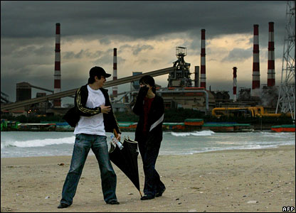 South Koreans walk along a beach in front of a steel mill