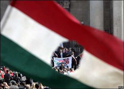 A hole in a flag reveals the protesters on the streets of the Hungarian capital, Budapest