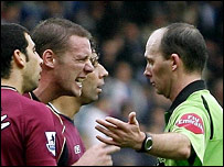 Kevin Nolan argues with referee Mike Dean