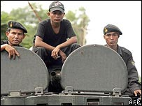 Cambodian soldiers sit on top of a military armoured vehicle
