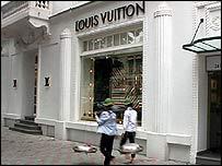 Peasants walking past a luxury shop in Hanoi