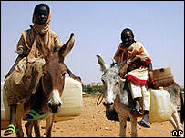 Two refugee girls leave Fata Borno's refugee camp to fetch water in Darfur, Sudan