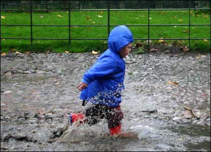 Boy splashing in the rain