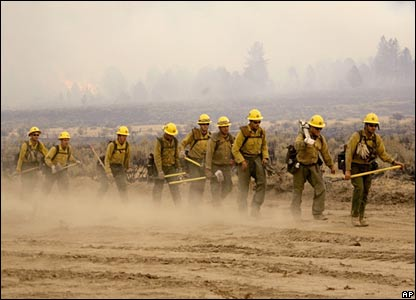 Firefighters walk along a road in Cabazon, California