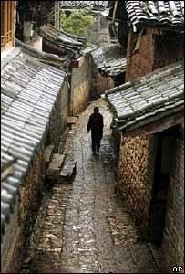 A Naxi ethnic minority man walks through the street in Suhe village near Lijiang