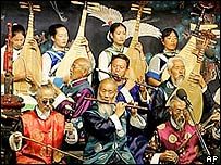 Naxi orchestra members play traditional songs for tourists