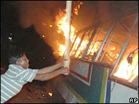 Opposition supporter attacks burning bus on Dhaka
