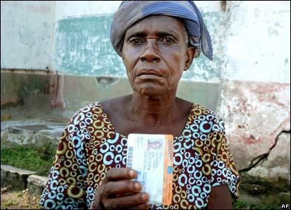 An elderly woman holds up her voter registration card outside a polling station in Bumba, in DR Congo.