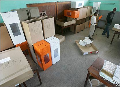 Elections officials stand among ballot boxes as they prepare for elections at Kinshasa.