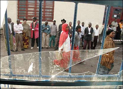 Voters seen through a broken window at a polling station in Goma, Congo.