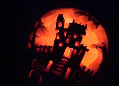Carved pumpkin with a house on a hill