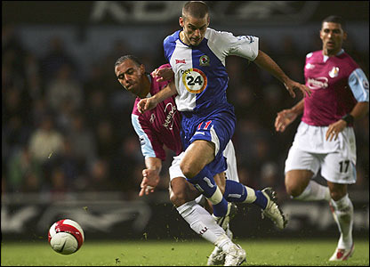 David Bentley is tackled by Anton Ferdinand