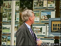 Man looks at houses for sale in an estate agents in Mayfair, London