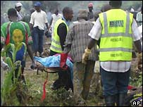 Red Cross workers carry away victims of a plane crash near Abuja, Nigeria