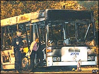 Police next to bus set ablaze by youths in Marseille