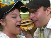The couple at work biting into a burger