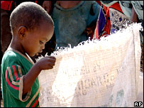 A boy in Kenya peers into a sack containing food aid (World Food Programme picture)