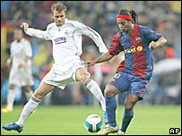 David Beckham (izq) marca a Ronaldinho, del Barcelona.