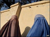 Two women clad in burqas wait for a bus in Kandahar, Afghanistan