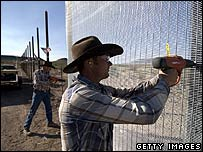Workers hired by the Minutemen erect a fence along the Arizona border with Mexico