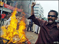 A protester next to burning debris in Dhaka on 28 October