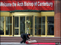 A Chinese hotel worker rolls out a red carpet in Beijing for the Archbishop of Canterbury
