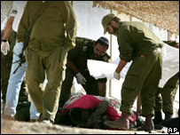 Israeli soldiers cover the body of a dead solider, killed during an operation in northern Gaza Strip town of Beit Hanoun