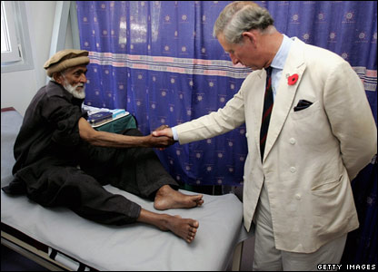 Prince Charles, the Prince of Wales, meets a patient in a new health clinic paid for by aid in Pattika in Pakistan-administered Kashmir