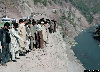 Men peer off a cliff face next to the main road to the village of Pattika in Pakistan-administered Kashmir