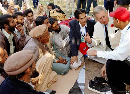Prince Charles, the Prince of Wales, crouches on the floor to listen to local farmers sitting cross legged on blankets in the shade in Pattika in Pakistan-administered Kashmir.