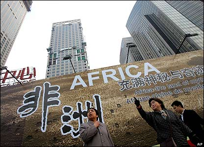 Chinese woman stand in front of a billboard which promotes the upcoming China-Africa summit meeting, outside a hotel in Beijing