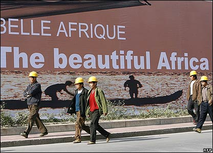Construction workers walk past a boarded-up construction site billboard in Beijing