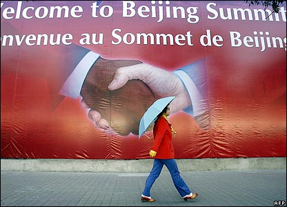 A woman with an umbrella walks past a billboard in Beijing announcing the African summit
