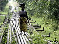 Woman walks across oil pipelines in Nigeria