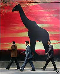 Chinese walk past a billboard of a giraffe