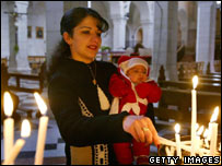 woman lighting candle at a Bethlehem church