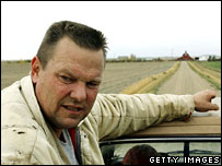 Democratic Senate challenger Jon Tester rides on the back of his pick-up truck on his farm