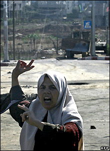 Palestinian woman and Israeli army bulldozer