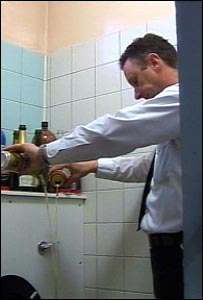 Police officer pouring the alcohol down a toilet