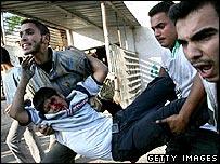 Men carry an injured teenager in Beit Hanoun