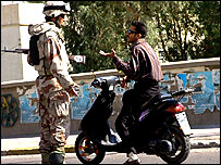 An Iraqi soldier checking a motorcyclist