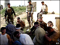 Iraqi army soldiers guard blindfolded suspects in Baquba on 28 October