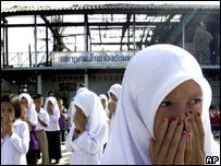A Thai schoolgirl prays outside her burnt-out school, the target of an attack by separatist rebels (1 Nov 2006)