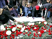 People lay flowers at the monument to the revolution