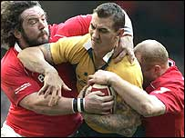 Wales prop Adam Jones (left) and Martyn Williams try to stop Australia fly-half Mat Rogers