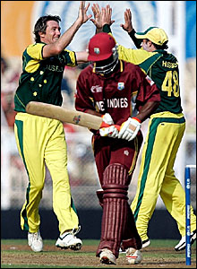 Runako Morton trudges off after being dismissed by Glenn McGrath (left)