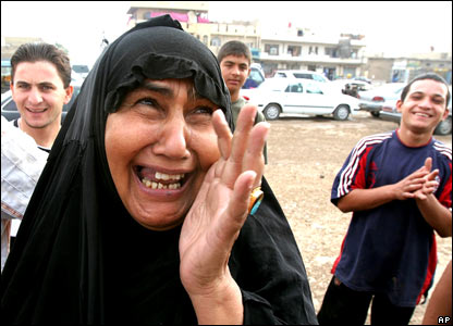 A Shia woman in Baghdad's Sadr City district wipes tears of joy from her eyes