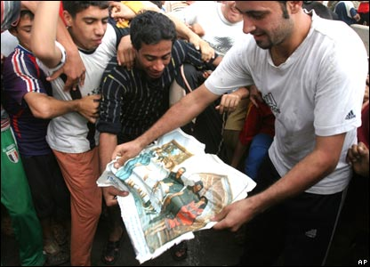 Iraqis in Baghdad's Shia City district celebrate the outcome of Saddam Hussein's trial by ripping up a poster