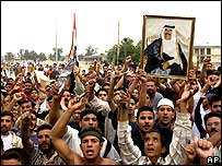 Iraqis hold up an image of Saddam Hussein as they protest his death sentence verdict, in his hometown of Tikrit,