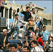 People cheering in Baghdad's Shia Sadr City district